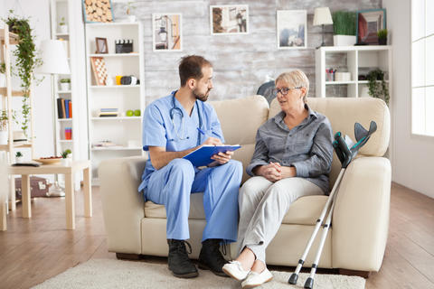 Male doctor with senior woman sitting on couch Photo