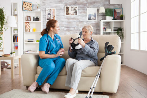 Elderly age woman sitting on couch with nurse Photo