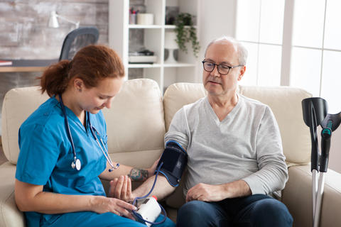 Female doctor reading blood pressure of old man Photo