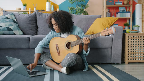 Creative African American girl playing the guitar learning with laptop from Live Action