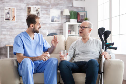 Bearded doctor in nursing home giving pills Photo