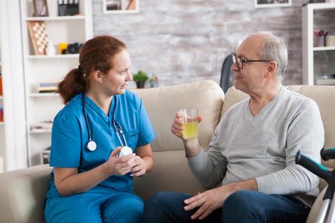 Senior man and lady nurse having a conversation Photo
