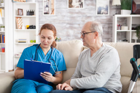 Female doctor with senior man sitting on couch in nursing home Photo
