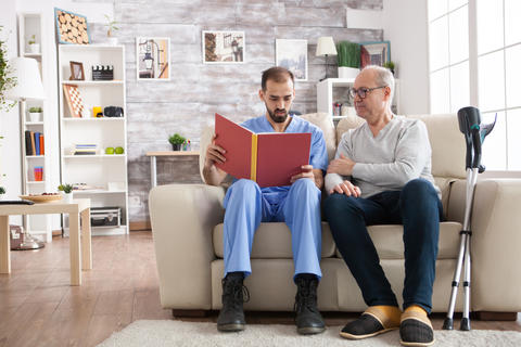 Bearded doctor reading a story in nursing home Photo