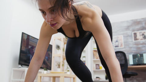 Young woman at home doing mountain climbers workout GIF