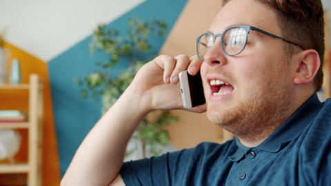 Emotional guy speaking on cellphone indoors in house smiling having fun Live Action