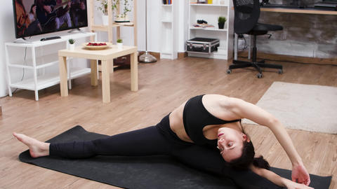 Female yoga practitioner doing a split on the mat GIF