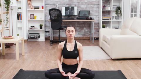 Fitness girl relaxing at home doing yoga meditation GIF