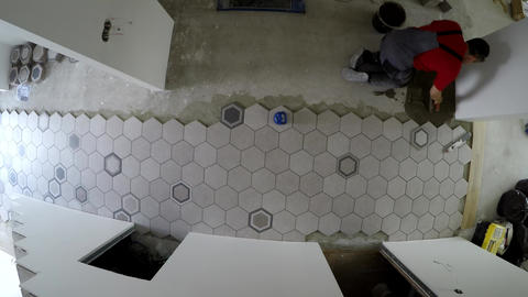 Professional worker laying hexagon stone mass tiles on floor. Timelapse Live Action