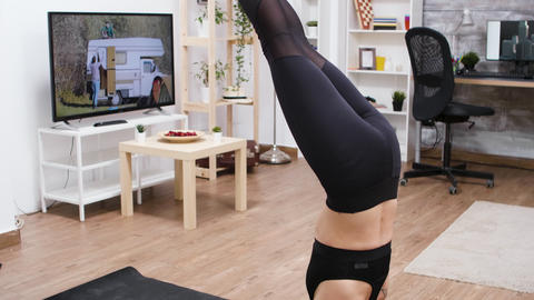 Caucasian woman at home practice yoga head stand GIF