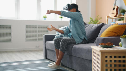 Afro-American lady in vr glasses is enjoying driving game at home moving arms Live Action