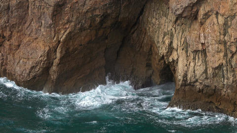 Sea waves enter a cave in rock and form splashes Stock Video Footage