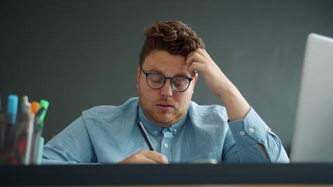 Exhausted guy writing taking notes feeling tired in office against gray Live Action