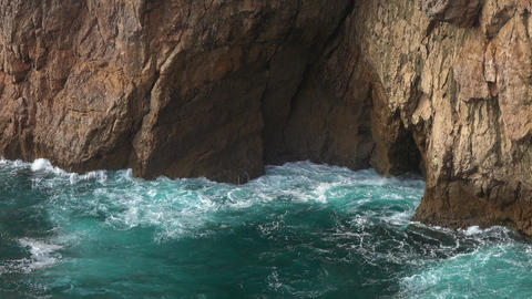 Sea waves enter a cave in rock and form splashes Live Action