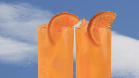 two glasses of rotating orange cocktails or plain orange juice with garnish Live Action