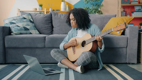 Mixed race young woman is learning to play the guitar using laptop at home 실사 촬영