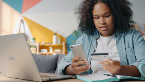 Joyful Afro-American student shopping online paying with smart phone and bank 실사 촬영