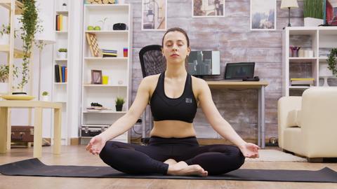 Beautiful young woman in sportswear practicing yoga GIF