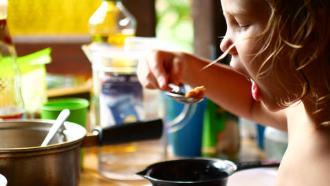 The child eats a spoon food from a pan Live Action