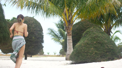 Woman on vacation running along the beach with white sand and palm trees Live Action
