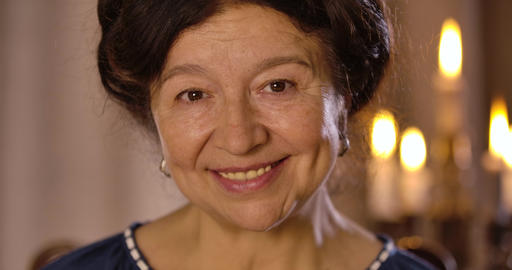 Close-up portrait of smiling mature Caucasian woman looking at camera and Live Action