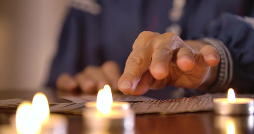 Extreme close-up of female Caucasian hands taking out cards from card deck lying Live Action