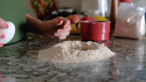 Woman cracking an egg on countertop and pouring it over flour ring Live Action