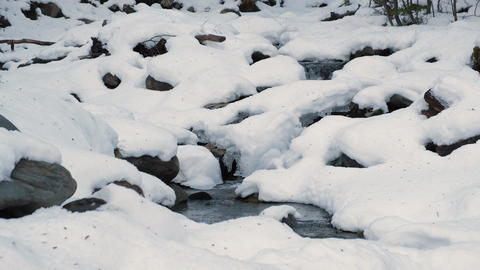Wide view of glaciar water brook flowing through snow covered rocks Live Action