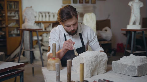 Attractive portrait of young talanted handsome sculptor which cleaning down the Live Action