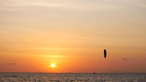 Sunset on the ocean, kite surfers ride on the sea Live Action