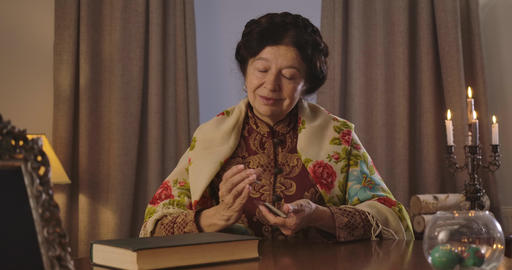 Brunette old Caucasian woman in shawl putting cards together and shuffling them Live Action