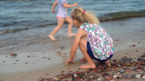 girl playing with wet pebble stones on coastline. Child washing hands in waves Live Action