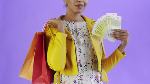 Portrait of african american woman with shopping bags and money fan on purple Live Action