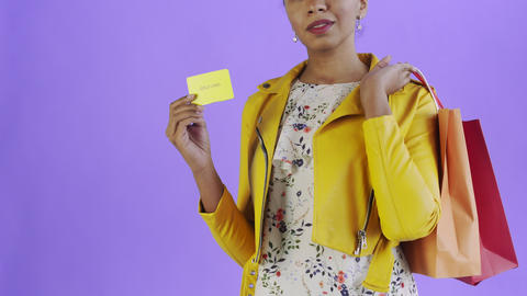 Portrait of african american woman with shopping bags and GOLD credit card on Live Action