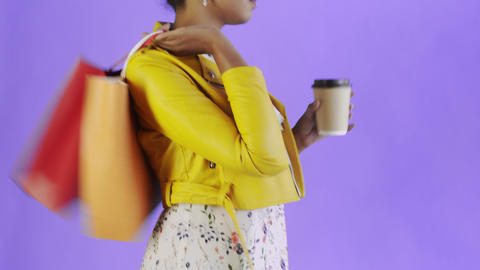 Portrait of african american woman with shopping bags is drinking a coffee on Live Action