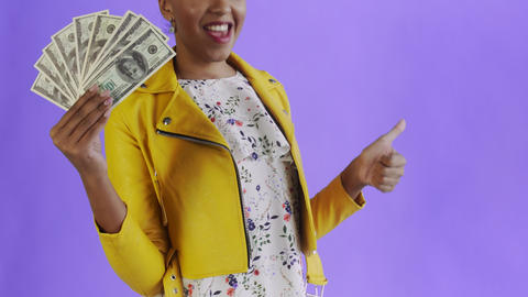 Satisfied african american woman with money is showing thumb up on purple Live Action