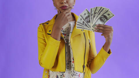 Thoughtful successful african american woman with money fan on purple Background Live Action