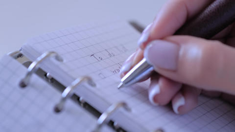 Close up - woman writing to do list in vintage notebook organizer - slow motion Live Action