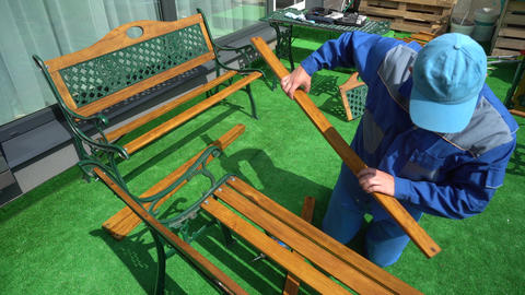 Man assemble furniture bench in outdoor garden yard. camera motion Live Action