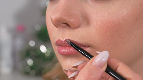 Applying makeup. The model's lips are painted with a makeup brush. Applying lip Live Action
