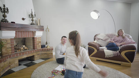 Portrait of playful Caucasian brunette girl dancing as her father playing Live Action