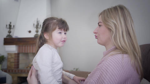 Portrait of playful Caucasian mother and daughter grimacing at home. Blond woman Live Action
