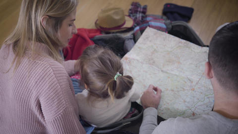 Back top view of young Caucasian family looking at map. Friendly father, mother Live Action