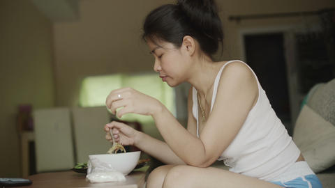Young Thai Woman is eating in living room Live Action
