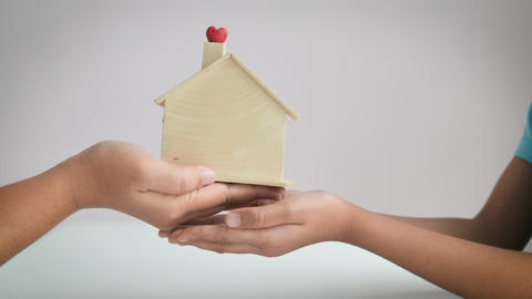 Close-up hands of mother giving wooden house model to the daughter metaphor family legacy real ライブ動画