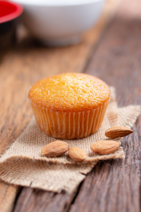 Close up a cup of almond cake against sack fabric on wooden tabl フォト