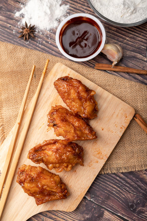 Hot and spicy Korean barbeque fried chicken on wood cutting boar フォト