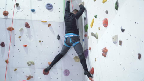 Muscular man practicing rock-climbing on a white rock wall indoors Live Action