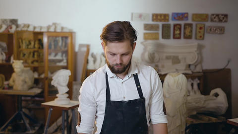 Attractive modern skilled bearded master in white shirt and apron standing with Live Action