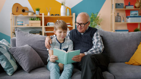 Old man grandfather reading book to smart grandchild indoors in apartment Live Action